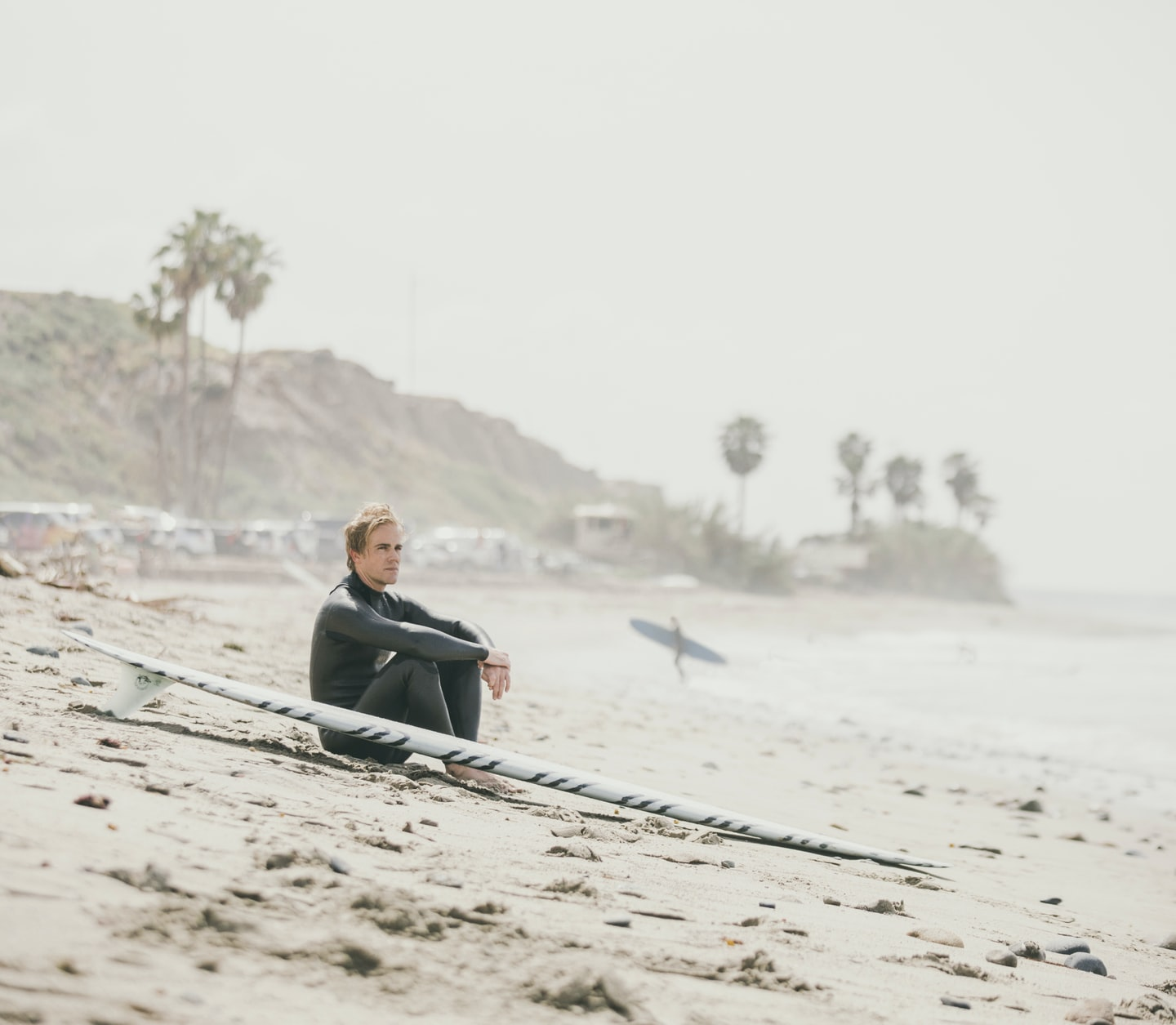 A man sitting on the beach next to his surfboard, looking into the distance.