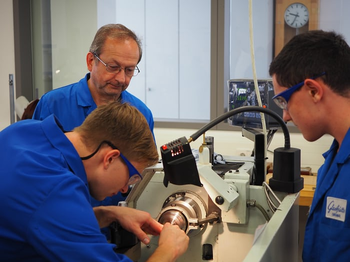 Lathe work being supervised by an instructor