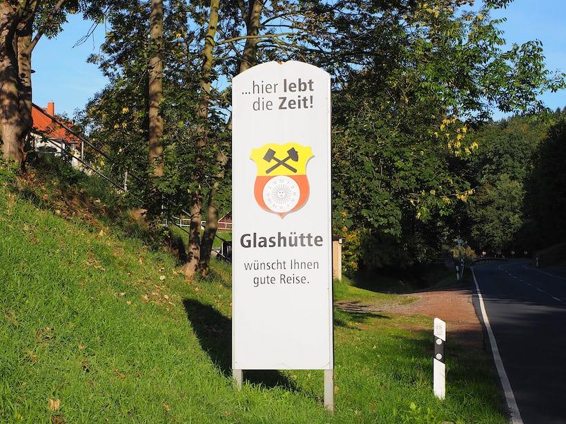 """Road sign, entering Glashütte. Rough translation via Google: """"Here lives the time, Glashütte wishes you a pleasant journey."""""""