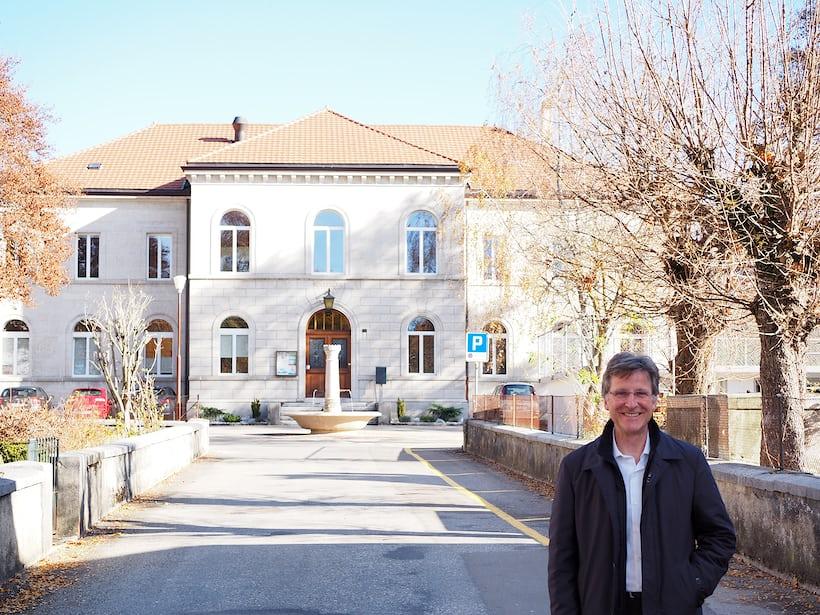 Michel Parmigiani outside a school he attended in Fleurier