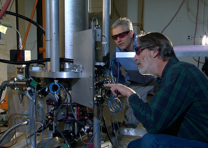 More details NIST physicists Steve Jefferts (foreground) and Tom Heavner with the NIST-F2 caesium fountain atomic clock, a civilian time standard for the United States.
