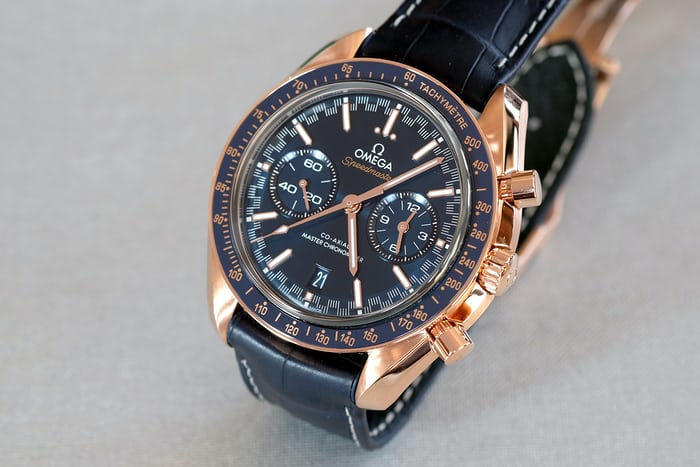 The gold model is paired with a dark blue dial, while the hands are also gold and the Speedmaster name are both golden.