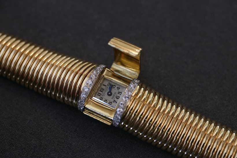 <p>You simply flip up the gold top on the bracelet to reveal the tiny watch underneath.</p>