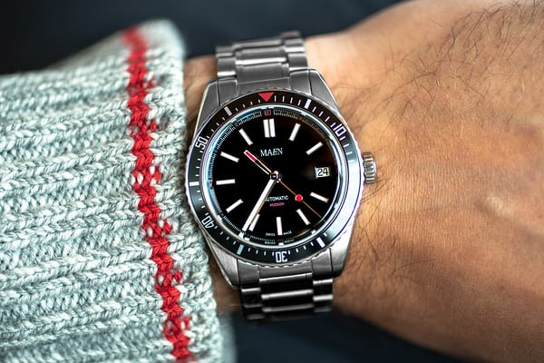 231c02aec0ab The Hudson s dial is sandblasted black with red accents