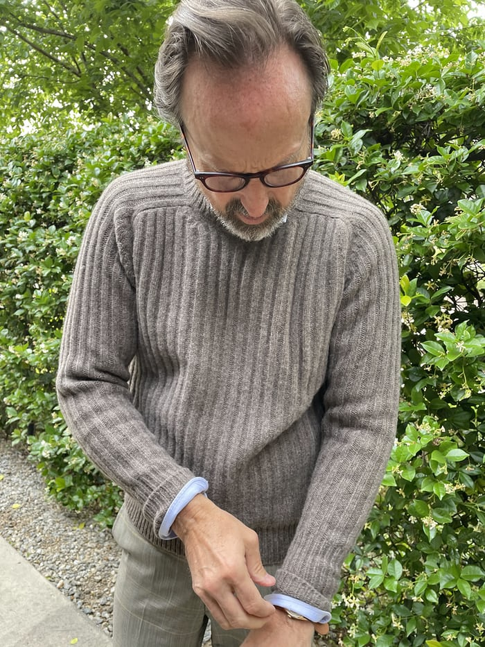A man in a sweater in front of a shrub